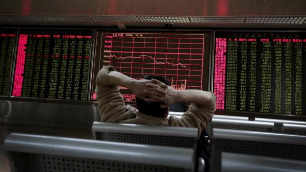 Ein Mann sitz auf einer Bank vor elektronischen Tafeln der Börse in Peking