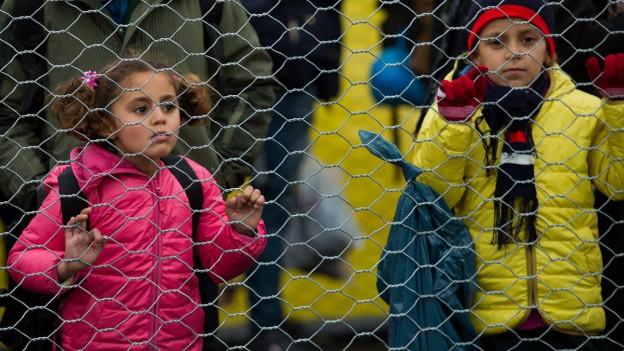 Zwei Kinder blicken durch Maschendrahtzaun.