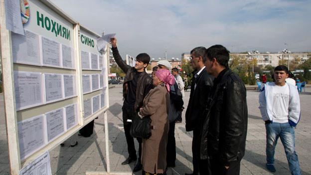 In Dushanbe stehen Arbeit suchende Leute vor einer Informationstafel, auf welcher freie Jobs angeboten werden.