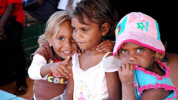 Drei Kinder spielen miteinander.