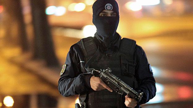 Ein bewaffneter türkischer Polizist steht vor brennenden Fahrzeugen im Zentrum Ankaras.