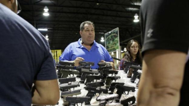Mann in einem blauen Hemd steht hinter einer Ausstellungsfläche, auf denen Pistolen ausgestellt sind.