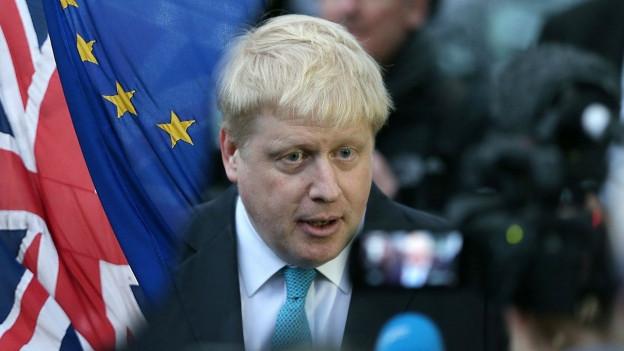 Grossaufnahme des blondon Boris Johnson bei seinem Pressestatement. Er wird umringt von Journalisten.
