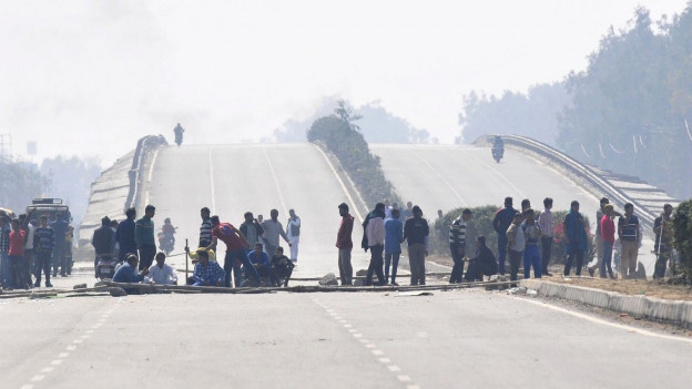 Auf einer sonst leeren Autobahn halten junge Männer eine Blockade ab.