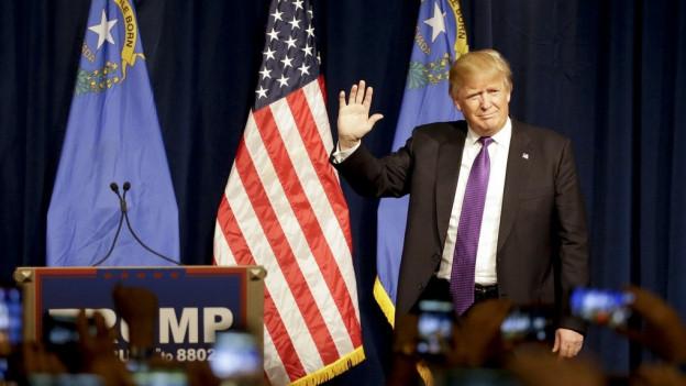 Trump auf einer Bühne, Flaggen, Mikrofone