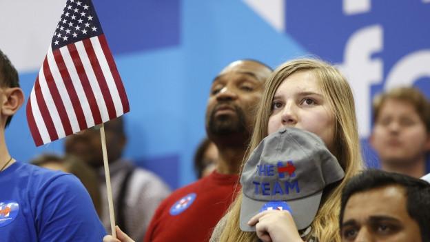Ausschnitt aus einer Menschenmenge an einer Vorwahlveranstaltung, in der Mitte des Bildes hält eine Frau ein US-Fähnchen in der Hand.