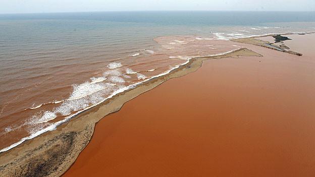 Blick auf das mit rostrotem Schlamm bedeckte Mündungsgebiet des Rio Doce.