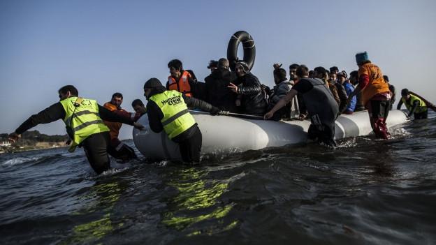 Frewillige Helfer ziehen ein Flüchtlingsboot an Land