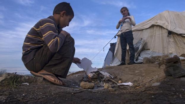 Ein junger Flüchtling versucht ein Feuer zu machen zwischen Griechenland und dem benachbarten Mazedonien.