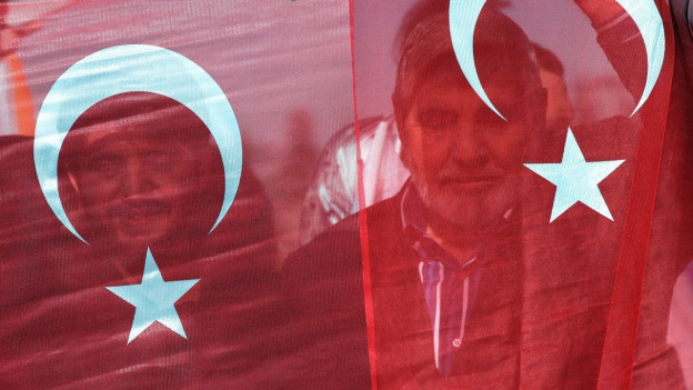 Zwei Türken halten die türkische Fahne vor ihrem Gesicht.