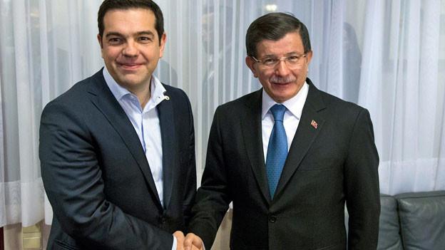 Lächeln für die Kamera: Alexis Tsipras und Ahmet Davutoglu der griechische und der türkische und der Premierminister reichen sich die Hand.