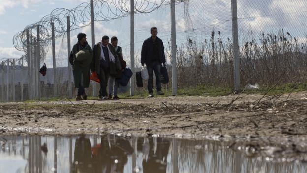 Flüchtlinge vor einem Grenzzaun in Mazedonien.