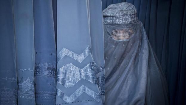 Eine afghanische Frau schaut durch den Sehschlitz ihrer Burka.