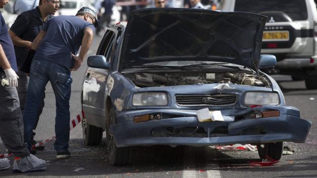 Männer schauen ins Fenster eines stark beschädigten Autos.