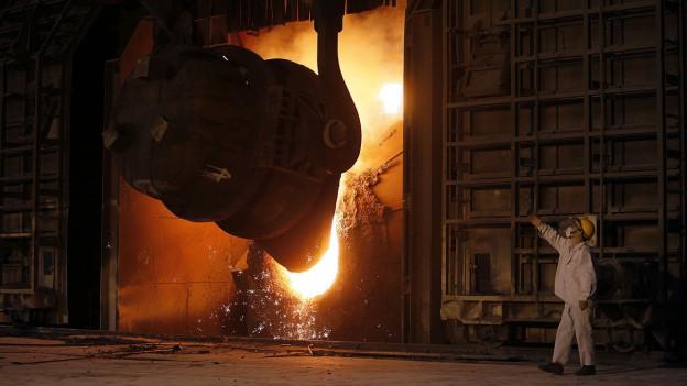 Ein chinesischer Stahlarbeiter in einer Fabrik kontrolliert die Stahlproduktion.