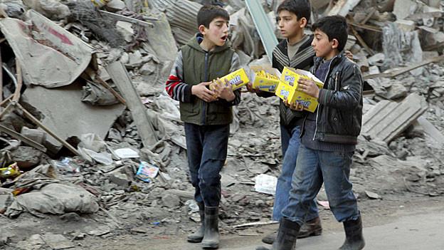 Drei Buben in den Trümmern von Aleppo.
