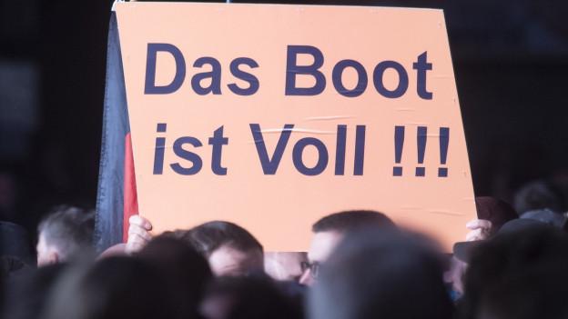 """Ein Plakat mit der Inschrift """"Das Boot ist voll"""" wird bei einer Kundgebung der rechtspopulistischen Partei AfD in die Luft gehalten."""