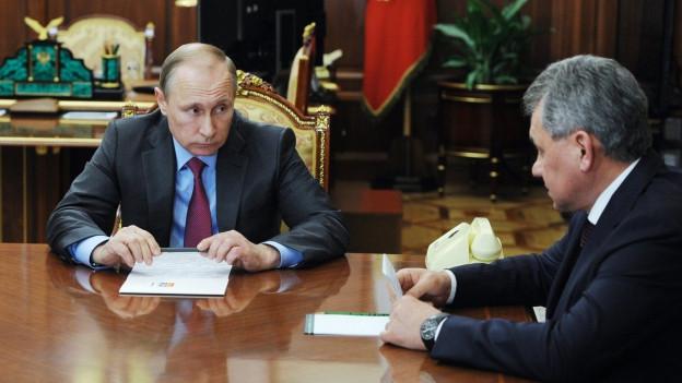 Aufnahme von Putin und Verteidigungsminister Shoygu. Sie sitzen beide an einem grossen Tisch aus dunklem Holz.
