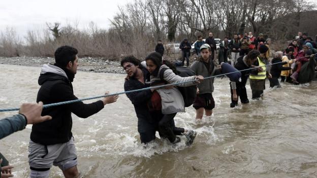 Flüchtlinge versuchen, einen Fluss zu durchqueren. Sie halten sich dabei an einem Stahlseil fest.