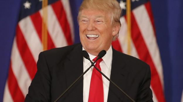 Lachender Mann vor US-Flagge.