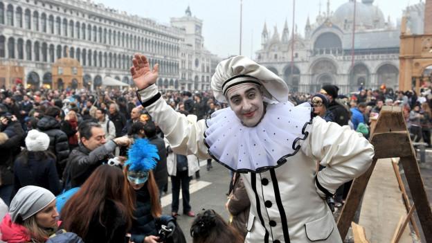 Ein verkleideter Mann zeigt eine Show auf dem St. Markusplatz in Venedig.