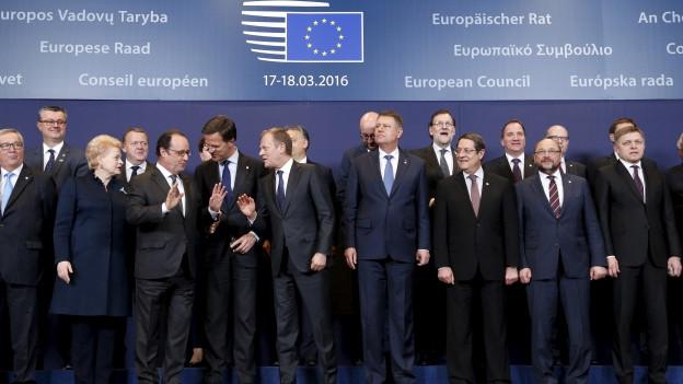 Männer und Frauen gruppieren sich vor EU-Logo.