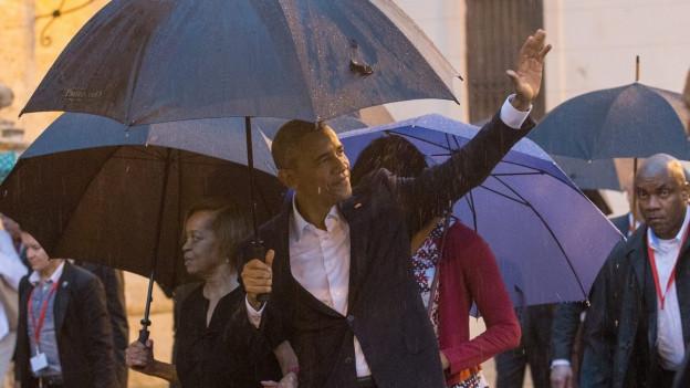 Barack Obama unter einem schwarzen Regenschirm, er hebt die Hand, um zu winken. Im Hintergrund die Altstadt von Havanna.