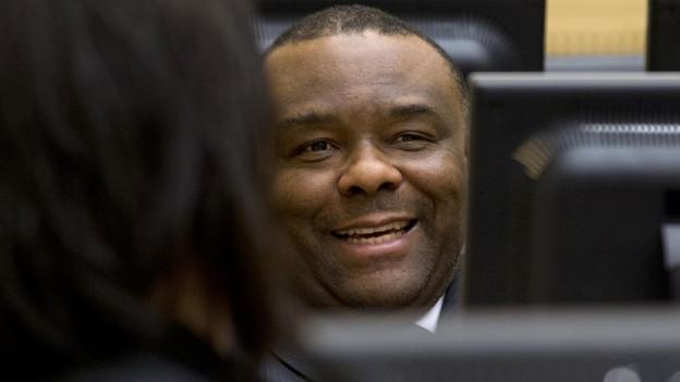 Nahaufnahme von Jean-Pierre Bembas Gesicht, das zwischen Computer-Monitoren zu sehen ist.