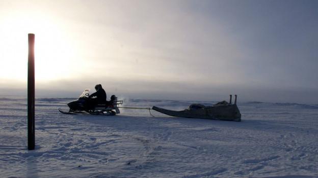Ein Inuit fährt mit seinem Schneemobil übers Eis.