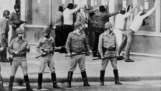 Menschen werden von Soldaten an einer Demonstration kontrolliert.