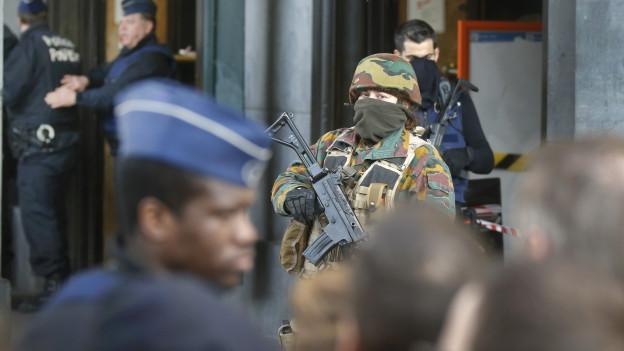 Ein vermummter Soldat mit Maschinenpistole bewacht den Bahnhof.