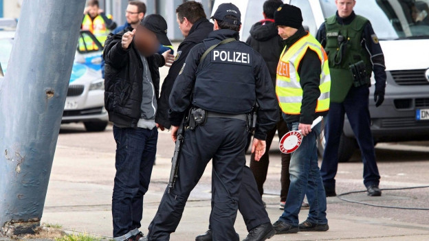 Polizeibeamte durchsuchen einen Mann am Strassenrand.