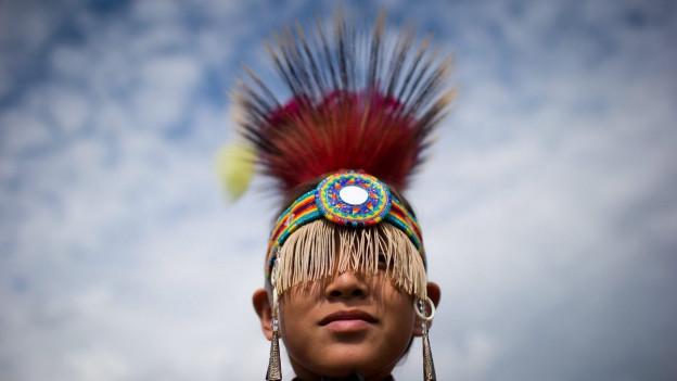 Ein junger Ureinwohner mit traditionellem, farbigem Kopfschmuck.
