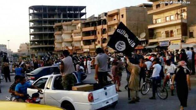 Das Bild zeigt beschädigte Häuser und IS-Kämpfer in Rakka.