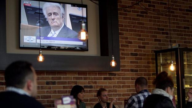 Menschen in einer Bar in Belgrad verfolgen die Urteilsverkündung von Radovan Karadzic am TV.