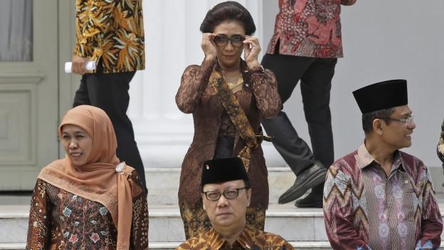 Indonesische Minister kommen die Treppe herunter, in der Mitte Susi Pudjastuti die neue Fischereiministerin.
