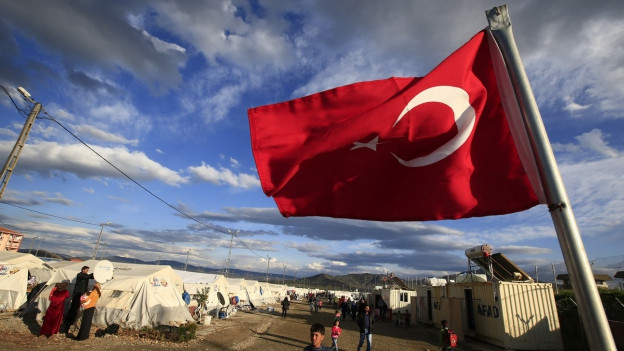 Im Vordergrund weht eine türkische Flagge, im Hintergrund weisse Zelte eines Flüchtlingslagers und einige Menschen.