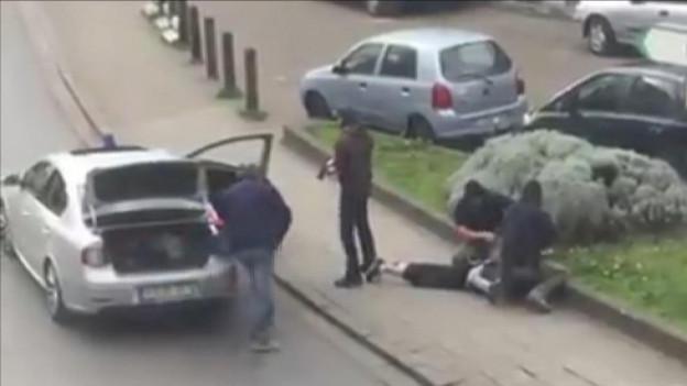 Ein Auto mit offenen Türen, daneben vier Polizisten in Zivil, die einen am Boden liegenden Mann fesseln.