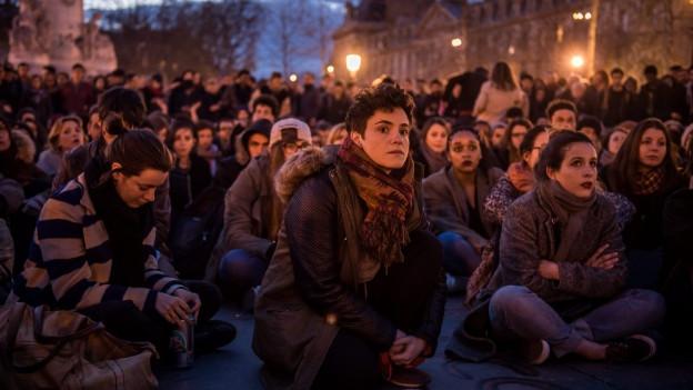 Demonstranten sitzen auf dem Place de la République in Paris.