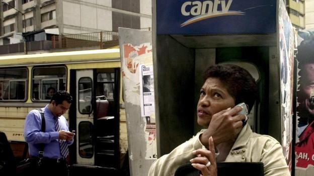 Eine Frau telefoniert vor einer Telefonzelle in Venezuela mit dem Handy.