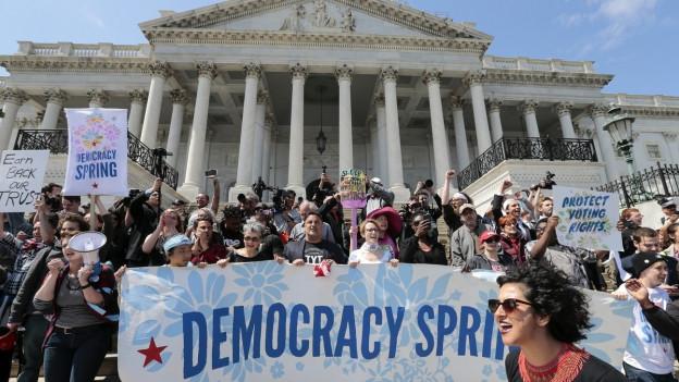 Eine Gruppe von Aktivisten hält vor dem Kapitol ein Transparent mit der Aufschrift «Democracy Spring» in die Höhe.