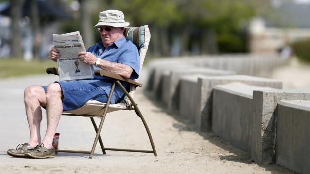 Ein Mann sitzt in einem Liegestuhl und liest eine Zeitung