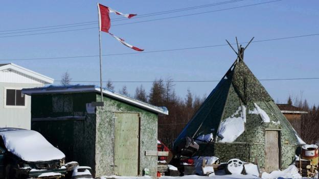 Ein Zelt und ein Haus in der kanadischen Gemeinde Attawapiskat, auf dem Haus weht eine zerrissene Flagge im Wind.