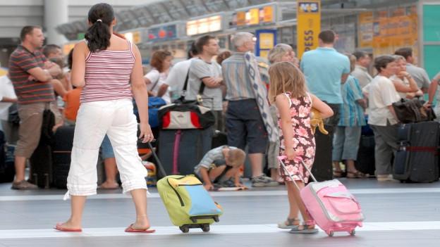 Flugpassagiere am Check-In am Flughafen Dresden, im Vordergrund eine Frau und ein kleines Mädchen von hinten, beide mit Rollkoffern.