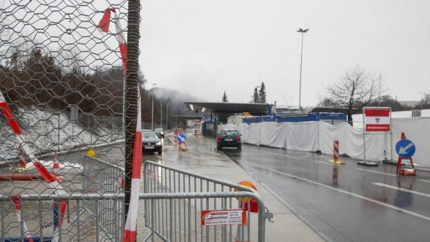 Strasse mit einem Grenzübergang, ein paar Gittern und Zäunen. Es herrscht kaum Betrieb, bloss ein Auto fährt richtung Grenzübergang.