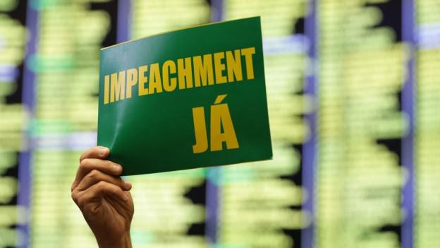 Ein Oppositionsparlamentarier hält ein Schild die Höhe mit der Aufschrift «Impeachment Jetzt»
