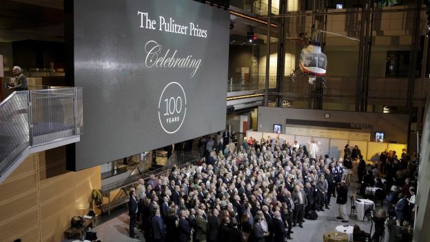 Ein scharzes Schild mit weisser Aufschrift «The Pulitzer Prizes», darunter steht eine Gruppen von Menschen.