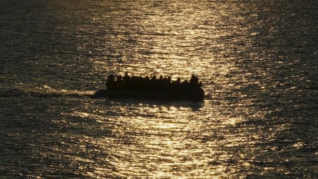Boot im Flüchtlingen auf dem Meer im Gegenlicht.