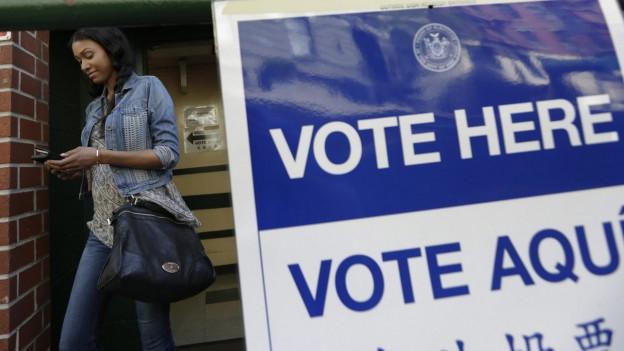 """Eine US-Stimmbürgerin verlässt ein Wahllokal in New York City, rechts im Vordergrund ist ein Plakat zu sehen, worauf """"Hier wählen"""" auf Englisch und Spanisch steht.."""