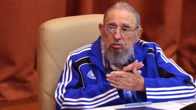 Ex-Staatschef Fidel Castro am Parteitag der Kommunisten auf Kuba, er trägt einen blauen Adidas-Trainer und eine Brille, sitzt an einem Pult und klatscht in die Hände.